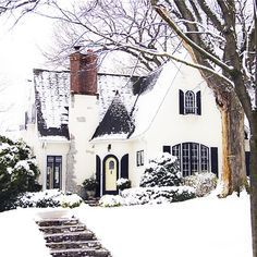 Beautiful home inspiration - Tutor style home exterior covered in snow with entry turret and black shutters.