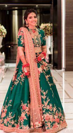 emerald green sabyasachi lengha w floral pattern blush pink details                                                                                                                                                                                 More