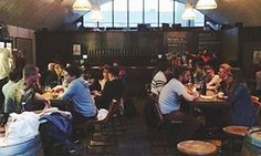 Drinkers sit at tables at Mother Kelly's, a bar in east London.
