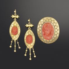 A Victorian Etruscan revival gold and coral cameo demi-parure -  Comprising an oval brooch with central coral corallium cameo depicting classical bust of a Bacchante, the gold brooch mount with wire and bead decoration; and a pair of earpendants en suite