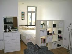 needs more color/decor but love the bookshelf at the foot of the bed. studio apartment
