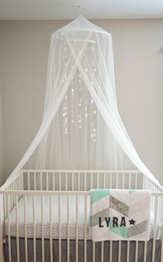 Crib and canopy from Ikea. Crib sheet: Pottery Barn. Grey linen crib skirt: Land of Nod. Quilt handmade by my sister. Star mobile handmade by me.