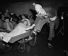 """Original Caption: New York: Actor Jimmy Stewart garbed in the role of """"Buttons"""" the clown from his new picture """"The Greatest Show on Earth"""" entertains some little Bellevue patients. Here, he clowns with a little girl in bed."""