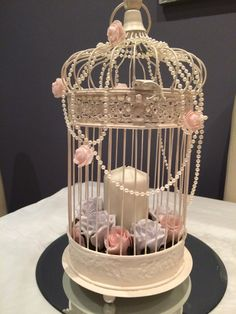 Pale pink and grey roses, candles and pearls in a shabby chic bird cage. Stunning bespoke wedding centrepieces in Wales from www.affinityeventdecorators.com