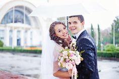 Trouwfoto in de regen met traditionele witte paraplu