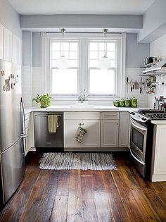 The light grey walls and white tiles, white cabinets and rich wood floors make this small kitchen welcoming as well as clean and crisp.