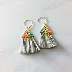 Japanese beads carefully woven by hand and small tassels made of silk yarn unearthed earrings Pattern: Geometric Triangles Color: Pink, gold, green, white, gray Pom poms: Silk grey yarn Earrings: 14 k gold-filled Diy Tassel Earrings, Tassel Jewelry, Fall Jewelry, Seed Bead Earrings, Beaded Earrings, Jewelry Crafts, Earrings Handmade, Beaded Jewelry, Beaded Bracelets