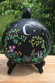 The Flower Garden at Night painted rock features a moon, stars, and a multi-colored floral design painted on the front and sides of a black background. The back of the rock is left in it's natural state and signed by yours truly. Painted Rocks For Sale, Hand Painted Rocks, River Stones, Rock Art, The Rock, Black Backgrounds, Etsy Store, Floral Design, Night