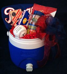 """""""Take Me Out to the Ballgame"""" -   Example includes 2 gallon Coleman cooler/drink dispenser with lid, Texas Ranger's t-shirt, Cracker Jacks, peanuts, Double Bubble gum, sunflower seeds, and Rawling's Official League baseball.      Estimated price as shown  $65.00"""