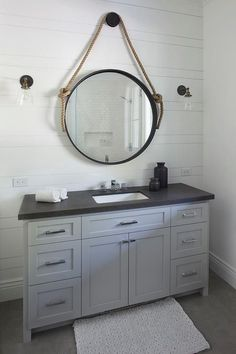 Exquisite cottage bathroom boasts a white bath mat placed in front of a steel gray washstand accented with a honed black granite countertop fitted with a sink and polished nickel faucet fixed beneath a rope convex mirror mounted to a shiplap wall between bronze and glass down-lit sconces.