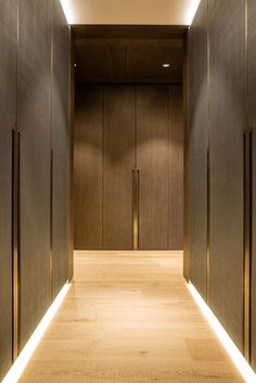 Case study - One Hyde Park, Knightsbridge. Design - Grangewood Finchatton. Joinery - INTERIOR-iD. Dressing Room with antique brass metal detailing, bespoke recessed handles fully integrated into framed wardrobe doors with woven leather and dark stained Zebrano timber.: