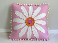 This decorative pillow features a classic white daisy with a whimsical fringed center, on a soft pink background. The creamy white pom pom