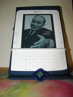 Cover made with this tutorial: www.chicaandjo.com/2009/09/03/make-a-custom-kindle-cover-.... I modified a bit (and made an error but I punted!). This is the open view. It sits up so the Kindle can be set on a table or (LOL), on your belly when lying  All of your Kindle needs.