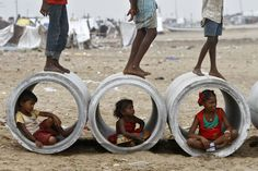 2013.10.10 - Children played in and around water pipes on a beach in Chennai, India (Babu/Reuters)