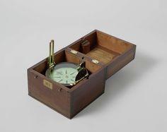 W. & T. Gilbert   Azimutkompas in houten doos, W. & T. Gilbert, c. 1810 - c. 1858   Azimutkompas in een houten doos. Het kompas heeft een vaste peilinrichting. Het oculair hiervan bestaat uit een prismatisch vizier om de roos te lezen, gecombineerd met een spleet-vizier met een zwart en groen verduisteringsglas; het draad-vizier aan de andere zijde is uitgerust met een kantelend zwart spiegeltje. De ketel is verzwaard met een loden gewicht onderaan. Met twee mechanieken in de ketel kan de…