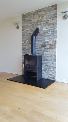 Charnwood C5 stove with wood store set on Honed Slate Hearth with Quartzite Veneer Cladding