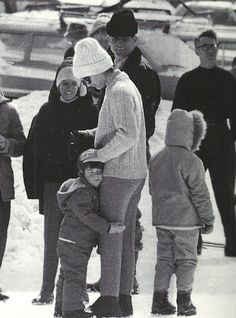 Before he tries his hand at skiing, John Jr. grabs hold of his mother's leg for moral support.