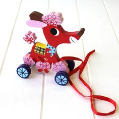 Wooden Pull Along Poodle  This colourful Pull Along Poodle has oodles of character! She is painted by hand and finished to perfection. This classy pooch is lightweight and easy to transport, just use her red ribbon to pull her along and watch as her blue decorated wheels spin and your smiling puppy rolls along. Wagging her tail as she trundles, she is sure to encourage little ones to get on their feet and start embarking on new adventures. Little girls will love taking this poodle for a…