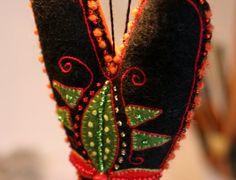 Svart hjärta av kläde. Broderat med lintråd, ylletråd och glaspärlor. Baksida av siden, nertill en vippa av kläde och pärlor. Sidentyget...