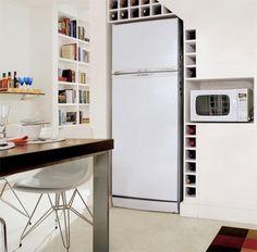 No vão sob a escada ficam o refrigerador, nichos de MDF para o microondas e ...