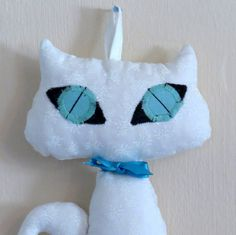 """Pretty white Cat Doll with a big turquoise eyes and a tiny ribbon around the neck that can be removed. This Cat Doll has been designed for decoration, made from my own original pattern and made of 100% high quality cotton and filled with acrylic. You can hang the doll on the wall, put it on a shelf or a sofa and she suitable even for a car or as decoration for your handbag. This black  The cat doll height: 8.3"""" (21cm) The cat doll face width: 4.7"""" (12cm) The cat doll can be gently washed by…"""