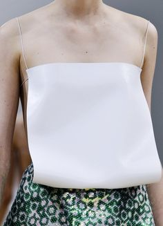 J.W. Anderson S/S 2014. Flat piece of fabric strapped to the body as a garment. The flat piece could serve another function once detached from the body. Maybe it could be s stiff fabric that could be folded into another object, from example a bowl.