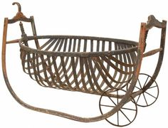 Primitive wooden field cradle, 19th c., the cradle of boat form suspended between the shaped frame having a pair of iron wheels on one end