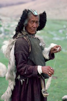 A woman yak herder, wearing a red & turquoise head-dress, spins yak wool whilst watching the herd. Nimaling Plateau. Ladakh. India. Note the spoon support suspended from her belt.