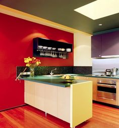 perfect kitchen for the small space - i love the blast of the colors and the back splash