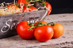 Fresh farmers tomatoes on wood table by Victoria Rusyn Shop on Creative Market