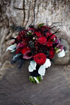 dyed black seeded eucalytpus, black feathers, callas, deep red dahlias, red roses and dusty miller.