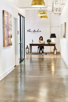 Bright industrial office space with gold pendant lights, concrete floors, and large art