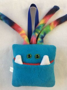 This listing is for a turquoise blue monster with green eyes and tie dyed hair. It measures approximately 6 inches square. The pocket is deep and sewn tightly to keep little treasures safe. The monster is stuffed with polyfil and has a handy ribbon for hanging. Interior of mouth pocket is red. The eyes are plastic safety eyes, which are intended for use in childrens toys because they are very secure and wont come loose. Each monster comes with a mini ziplock tooth bag, and an official Fang…
