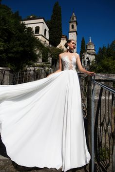Liana - White Desire - MillaNova Fascinating A-line Liana wedding gown is made of royal chiffon, beautiful rayon and classy lace. The hem of the romantic fluttering skirt falls to the floor. The lace decorated corset has a deep décolleté and is beautifully buttoned up on the back.