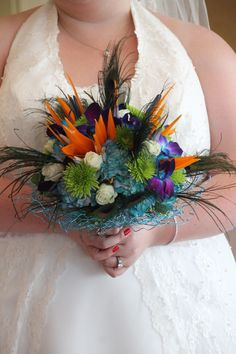 Bright colorful wedding bouquet, bird of paradise, blue purple orchids, peacock feathers. Created by Judith Marie at Fox Bros Floral, Hartland, WI