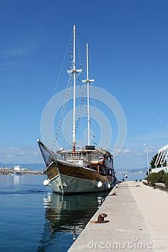 Vintage sailboat docked on local pier and tied with thick sailor rope to iron mooring bollards. Calm sea reflects clear blue sky.