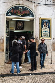People standing in line outside a Ginjinha shop in Lisbon, Portugal