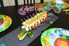 Gurkenkrokodil Dschungel  Einfach eine Salatgurke waschen, den unteren Teil ein wenig abschneiden damit sie nicht wegrollt. Aus dem unteren Teil kann man dann die Füße schneiden. Dann vorne das Maul einschneiden und Zähne mit einem Messer reinschneiden. Dann mit einem Schäler ein breites Stück einer Karotte abschälen und als Zunge verwenden. Auf die Zunge wird dann ein Stück Käse oder Tomate gelegt um das Krokodilsmaul offen zu halten. Dann nimmt man kleine Mozzarella-Kugeln und schneidet…