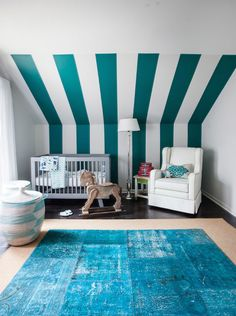 Stunning nursery features teal striped sloped ceiling over Babyletto Hudson Crib situated next to wingback glider paired with accent table illuminated by polished nickel floor lamp alongside Senegal basket atop turquoise overdyed rug layered over bound sisal rug.