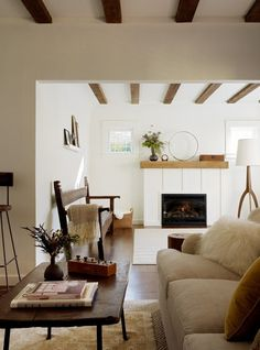 Ceiling beams and white simple fireplace with rustic mantle!!! On our to do list!