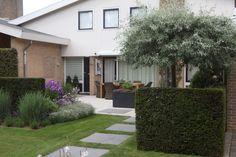 Een groene strakke #tuin met prachtig gras en grote vierkante tegels.