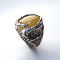 Lovely design, but I wonder how soon that spire of silver gets caught on something and bent all over the place?    Twisted And Trapped Ring Yellow  by Carrie Bilbo Art Jewelry