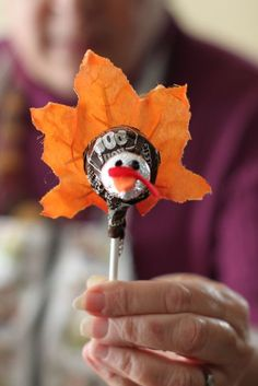 """Imitation leaf  Brown Tootsie Pop Hershey's Kiss  two black beads for the eyes  orange felt triangle for the beak  red felt for """"whatever that gobbly thing is.""""   All glued together."""