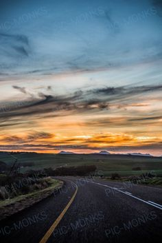 Another stunningly beautiful shot of an inviting road with the sun setting over a rolling landscape. Driving can be such a joy on such roads - and the journey becomes more memorable than the destination.Nature is unquestionably the most gifted artist! Look at those cottony clouds, a perfect blue sky, and that gorgeous glow of sunset!