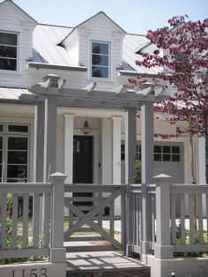 Charming: all of it, the home is cute, but look at the pergola, the gate, and fence.