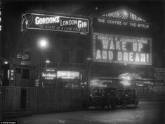 Electric signs outside the London Pavilion in Piccadilly Circus, advertising the Charles B Cochran revue 'Wake Up and Dream!', as well as Gordon's Gin, State Express cigarettes and the Ever Ready razor