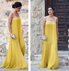 Sara Carbonero deslumbró en la boda de su prima Marina con este vestido amarillo plisado de inspiración griega firmado por Cortana. Lo combinó con un divertido clutch en forma de manzana de Uterqüe y lució un sencillo pero elegante recogido.