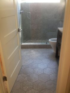 This guest bathroom hexagon tile for the floor and shower walls is AKDO Heritage Blend with accents by Jaskba's Natural Glamour and AKDO Origin.
