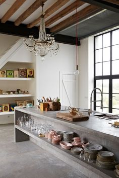 a concrete kitchen with a big old chandelier