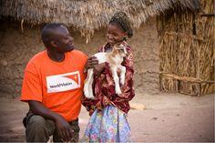 World Vision staff, Joseph Kavalu, with a sponsored child, Binta Balde, who received her new baby goat through World Vision. (Photo: 2010 David duChemin/World Vision)